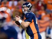 Oct 19, 2014; Denver, CO, USA; Denver Broncos quarterback Peyton Manning (18) passes for a touchdown in the first quarter against the San Francisco 49ers at Sports Authority Field at Mile High. Mandatory Credit: Ron Chenoy-USA TODAY Sports