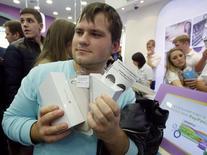 Un cliente sostiene cajas de teléfonos iPhone 6 de Apple en una tienda en Moscú, sepo 26 2014. El fabricante de dispositivos tecnológicos Apple Inc reportó un alza de sus ingresos de un 12 por ciento, mayor a la esperada, porque el lanzamiento de su nuevo iPhone ayudó a impulsar ventas de 39,27 millones de teléfonos avanzados en el trimestre terminado en septiembre. REUTERS/Maxim Shemetov