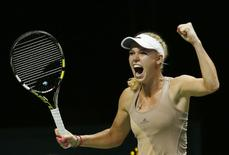 Caroline Wozniacki of Denmark celebrates her win over Maria Sharapova of Russia during their WTA Finals singles tennis match at the Singapore Indoor Stadium October 21, 2014. REUTERS/Edgar Su