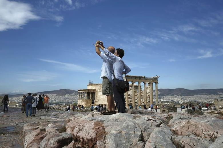 Tourists take photographs during their visit on the Acropolis hill on the eve of World Tourism Day (WTD) in Athens September 26, 2014.   REUTERS/Yorgos Karahalis