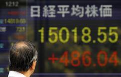 Un transeúnte observa una pantalla digital mostrando índices económicos en Tokio. Imagen de archivo, 20 octubre, 2014.  Las bolsas de Asia subían el miércoles luego de que los resultados optimistas de dos referentes del sector tecnológico estadounidense y las esperanzas de un nuevo estímulo del Banco Central Europeo contrarrestaron las preocupaciones sobre las perspectivas de la economía global. REUTERS/Yuya Shino