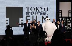 "Directors of ""Big Hero 6 "" Don Hall (L) and Chris Williams (3rd L) wave with Japanese actress Miho Kannno (2nd L) as Chief Creative Officer of Pixar and Walt Disney Animation Studios, John Lasseter (4th L), and the producer Roy Conli (3rd R), Japanese actor and son of former Prime Minister Junichiro Koizumi, Kotaro Koizumi (2nd R), and Disney Animation Studio Executive Vice President Andrew Millstein (R) attend the opening event of the Tokyo International Film Festival before the world premiere of their film ""Big Hero 6 "" in Tokyo October 23, 2014.  REUTERS/Yuya Shino"
