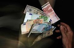 Евро и доллары на фотографии, сделанной в Праге 23 января 2013 года. REUTERS/David W Cerny