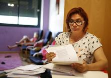 Unemployed hairdresser and mother-of-three Yasmin Rubiano looks at documents at her flat in Madrid June 30, 2014. Picture taken June 30, 2014.    REUTERS/Juan Medina