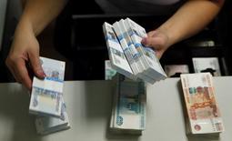 """Сотрудник московского банка пересчитывает купюры 2 сентября 2014 года. Рубль в пятницу утром обновил минимумы, а ЦБР возобновил продажу валюты и сдвиги коридора из-за рисков снижения российского кредитного рейтинга до """"мусорного"""" статуса агентством S&P, которое сообщит о своем решении сегодня ночью, а также в условиях локального спроса на валюту при отсутствии доступа к зарубежным денежным  REUTERS/Maxim Zmeyev"""