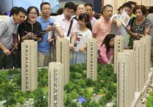 Personas miran una maqueta de una nueva instalación habitacional en una exhibición en Hangzhou. Imagen de archivo, 17 agosto, 2014. Los precios de las casas chinas cayeron por quinto mes consecutivo en septiembre, borrando las ganancias de un año y aumentando las expectativas de que el Gobierno tendrá que ofrecer un estímulo adicional para amortiguar el golpe a la economía. REUTERS/Stringer