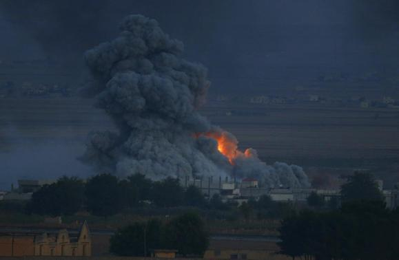 Smoke rises over the Syrian town of Kobani after an airstrike, as seen from the Mursitpinar crossing on the Turkish-Syrian border in the southeastern town of Suruc in Sanliurfa province October 24, 2014. REUTERS/Kai Pfaffenbach