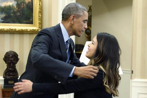 President Barack Obama leans over to hug Dallas nurse Nina Pham while meeting with her in the Oval Office in Washington, October 24, 2014.    REUTERS/Larry Downing