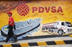 Un trabajador pasa frente a un mural de PDVSA en una estación de gasolina en Caracas. Imagen de archivo, 29 agosto, 2014. Suena vergonzoso: Venezuela, el país miembro de la OPEP con las reservas petroleras más grandes del mundo, está importando crudo por primera vez en su historia. REUTERS/Carlos Garcia Rawlins
