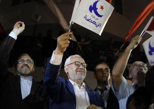 Rached Ghannouchi, leader of the Islamist party Ennahda, waves the party flag outside Ennahda's headquarters in Tunis  October 27, 2014. REUTERS/Zoubeir Souissi