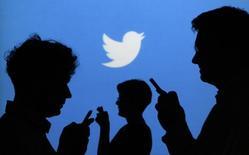 Силуэты людей с мобильными устройствами на фоне логотипа Twitter в Варшаве 27 сентября 2013 года. Сеть микроблогов Twitter Inc сообщила в понедельник о снижении показателя активности пользователей на 7 процентов, хотя их общее число выросло в третьем квартале на 23 процента. REUTERS/Kacper Pempel