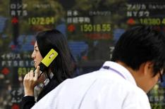 Una persona que habla por teléfono pasa frente una pantalla electrónica que muestra índices económicos en Tokio. Imagen de archivo, 20 octubre, 2014.  Las bolsas de Asia avanzaban y el dólar cotizaba estable el martes, mientras los inversores esperan el resultado de la reunión de dos días de la Reserva Federal de Estados Unidos que comienza más tarde en la sesión para obtener pistas sobre la dirección de las tasas de interés en ese país. REUTERS/Yuya Shino