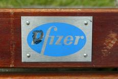 Логотип Pfizer на скамейке в Рингаскидди 11 июня 2003 года. Квартальные результаты Pfizer Inc <PFE.N> оказались лучше прогнозов аналитиков благодаря росту продаж лекарств от рака и растущему спросу на развивающихся рынках, сообщила компания во вторник.  REUTERS/Paul McErlane