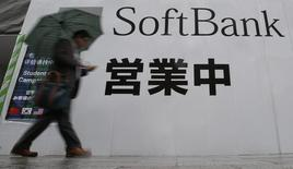 A man holding an umbrella walks past the logo of Softbank Corp at its branch in Tokyo April 22, 2014. REUTERS/Yuya Shino