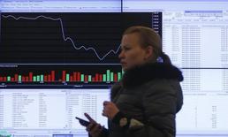 Женщина проходит мимо экрана с котировками на Московской бирже 14 марта 2014 года. Рублевые цены российских акций повышаются в среду третью сессию подряд, а валютный индикатор РТС остается под давлением дешевеющего рубля. REUTERS/Maxim Shemetov