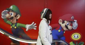 """Покупатель в магазине электроники в Токио 20 января 2014 года. Переживающий непростые времена японский производитель видеоигр Nintendo Co сумел получить опередившую прогнозы аналитиков операционную прибыль во втором квартале финансового года благодаря игре """"Mario Kart 8"""", поддержавшей продажи консоли Wii U. REUTERS/Yuya Shino"""