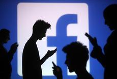 Siluetas de personas con sus dispositivos móbiles frente a una pantalla con el logo de Facebook en Zenica, 29 octubre, 2014. Otro día, otro informe trimestral de una empresa tecnológica que decepciona a los inversores.         Las acciones de Facebook cayeron un 7,4 por ciento a 74,78 dólares en las primeras operaciones del miércoles, un día después de que la compañía reveló planes de gasto agresivos para 2015.   REUTERS/Dado Ruvic