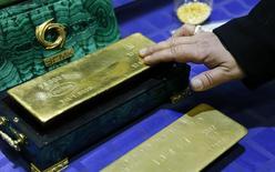 Un empleado toca una barra de oro de la firma Uralelektromed en Verkhnyaya Pyshma, Rusia, oct 17 2014. El oro caía el miércoles mientras los inversores esperan pistas de la Reserva Federal sobre si reafirmará su disposición a esperar un período prolongado de tiempo antes de subir las tasas de interés. REUTERS/Maxim Shemetov