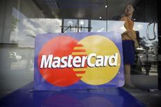 Una persona atrás del logo de Mastercard en Myanmar, en Yangon. Imagen de archivo, 15 noviembre, 2012.  MasterCard Inc, la segunda mayor compañía mundial de tarjetas de crédito y débito, reportó un aumento de 15,5 por ciento en sus ganancias trimestrales debido a que a más clientes usaron sus tarjetas para hacer compras. REUTERS/Soe Zeya Tun