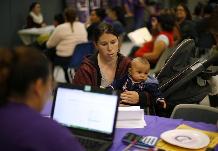 Mary Estrada, 29, holds her six-month-old daughter Lucille Estrada as she looks into signing up for health insurance at a health insurance enrollment event in Cudahy, California March 27, 2014. REUTERS/Lucy Nicholson