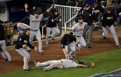 San Francisco Giants third baseman Pablo Sandoval (bottom) celebrates with teammates after catching a pop out for the final out of game seven of the 2014 World Series against the Kansas City Royals  at Kauffman Stadium. REUTERS/USA Today Sports/Denny Medley