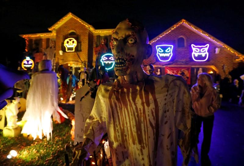 a visitor to a house covered in halloween decorations looks over the scene in the front yard in the chicago suburb of naperville illinois october 27