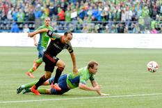 Oct 25, 2014; Seattle, WA, USA; Los Angeles Galaxy forward Landon Donovan (10) and Seattle Sounders FC defender Chad Marshall (14) fight for the ball during the first half at CenturyLink Field. Mandatory Credit: Steven Bisig-USA TODAY Sports
