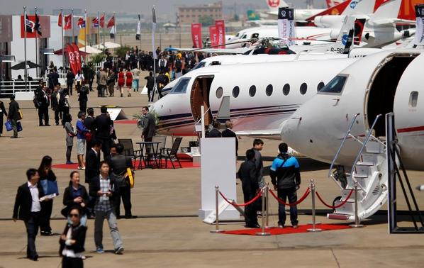 Guests walk next to aircraft during the Asian Business Aviation Conference and Exhibition (ABACE) at Hongqiao International Airport in Shanghai in this April 15, 2014 file photograph. REUTERS/Carlos Barria/Files