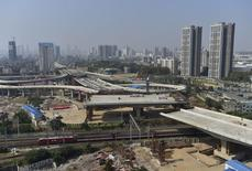 An overpass is seen under construction as a train travels past in Wuhan, Hubei province, October 24, 2014. REUTERS/Stringer/Files
