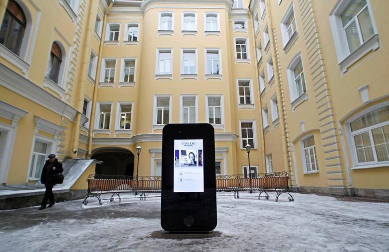 A man walks past a recently erected iPhone-shaped monument in memory of Apple's late co-founder Steve Jobs in the yard of the State University of Information Technologies, Mechanics and Optics in St. Petersburg January 10, 2013.  REUTERS/Alexander Demianchuk
