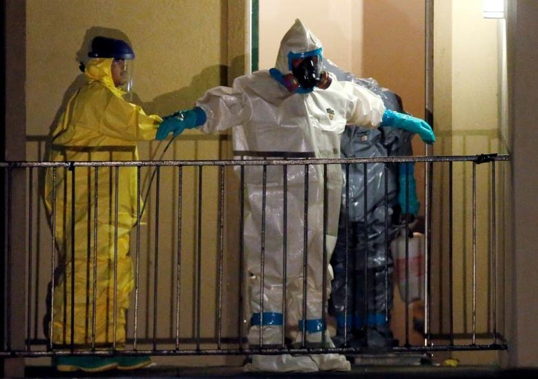 A worker in a hazardous material suit is sprayed down by a co-worker after coming out of an apartment unit where a man diagnosed with the Ebola virus was staying in Dallas, Texas, October 5, 2014. REUTERS/Jim Young