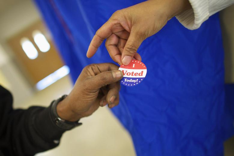 Voting machine operator Robin Coffee-Ruff hands a sticker to a voter who cast his ballot at West Philadelphia High School on U.S. midterm election day morning in Philadelphia, Pennsylvania, November 4, 2014.  REUTERS/Mark Makela
