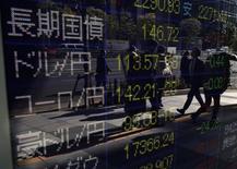Экран с курсами валют у брокерской конторы в Токио 4 ноября 2014 года. Азиатские фондовые рынки, кроме Японии, снизились в среду за счет отдельных отраслей и слабой экономической статистики Китая. REUTERS/Yuya Shino