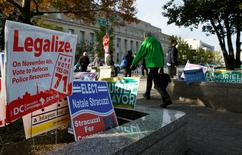 Pedestrians pass by a DC Cannabis Campaign sign in Washington November 4, 2014.           REUTERS/Gary Cameron
