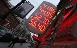 Табло с курсами валют в Санкт-Петербурге 5 ноября 2014 года. Рубль дешевеет в четверг, продолжая искать нижнюю точку после решения Центробанка отменить нелимитированные интервенции, ограничившись $350 миллионами в день, но с возможностью дополнительных интервенций. REUTERS/Alexander Demianchuk