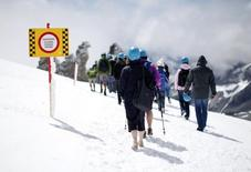 Tourists walk in the snow at the Hintertuxer Glacier in the Austrian province of Tyrol August 10, 2011. REUTERS/Lisi Niesner
