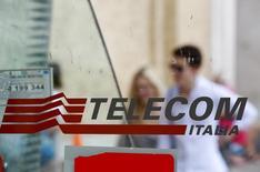 Personas pasan atrás del logo de Telecom Italia en una casilla telefónica en Roma. Imagen de archivo, 28 agosto, 2014.  Telecom Italia SpA informó el viernes de una caída de un 7,7 por ciento en su beneficio operativo a septiembre, arrastrada por su negocio local, golpeado por la recesión, y la desaceleración en Brasil, pero la firma dijo que veía señales concretas de recuperación en el mercado italiano. REUTERS/Max Rossi