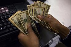 """Un cajero contando dólares en una tienda en Nueva York, nov 28 2013. Argentina dijo el viernes que licitará un bono nominado en dólares estadounidenses y pagadero en pesos vinculado a la evolución del tipo de cambio (""""dollar linked"""") por un monto de hasta 1.000 millones de dólares. REUTERS/Eric Thayer"""