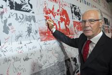 Former player and coach Franz Beckenbauer signs a wall of fame at a gala marking the 50th anniversary of the foundation of the German Bundesliga soccer league, in Berlin August 6, 2013.  REUTERS/Thomas Peter