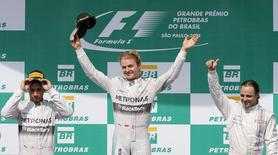 (L-R): First runner up Mercedes Formula One driver Lewis Hamilton of Britain, winner Mercedes Formula One driver Nico Rosberg of Germany and second runner up Williams Formula One driver Felipe Massa of Brazil react during the podium ceremony after the Brazilian Grand Prix in Sao Paulo November 9, 2014. REUTERS/Paulo Whitaker