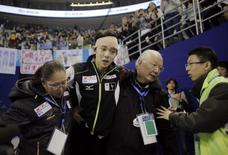 Yuzuru Hanyu of Japan is helped by coaches as he leaves the arena after competing at the men's free skating program during the Cup of China ISU Grand Prix of Figure Skating in Shanghai November 8, 2014.  REUTERS/Carlos Barria