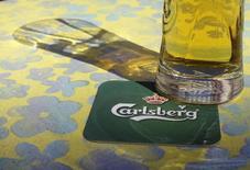 Логотип Carlsberg на подставке под пивной бокал в Риге 6 мая 2013 года. Пивоваренная компания Carlsberg сообщила в понедельник о росте продаж в третьем квартале, а ее скорректированная операционная прибыль совпала с ожиданиями аналитиков.  REUTERS/Ints Kalnins