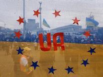 Участники акции протеста на фоне украинского флага, украшенного звездами с флага ЕС, в Киеве 15 декабря 2013 года. Вид развевающегося над баррикадами в Киеве голубого с золотым флага вдохновлял Евросоюз, оживляя в памяти его собственный образ оплота демократии на фоне сомнений и сумрачных экономических перспектив. Но почти через год после первых протестов Евромайдана, отобравшего власть у прокремлёвского президента за отказ от торгового соглашения с Европой, кое-кто в Брюсселе разочарован опытом помощи Украине. REUTERS/Alexander Demianchuk
