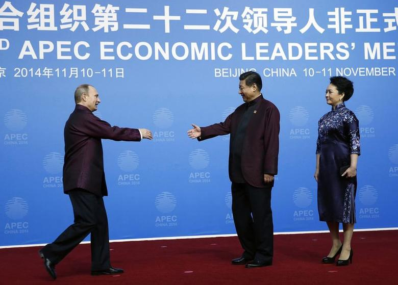 Russia's President Vladimir Putin (L), in traditional Chinese-style outfit, shakes hands with China's President Xi Jinping as Xi's wife Peng Liyuan stands beside, during the APEC Welcome Banquet, at Beijing National Aquatics Center, or the Water Cube in Beijing, November 10, 2014. REUTERS/Kim Kyung-Hoon