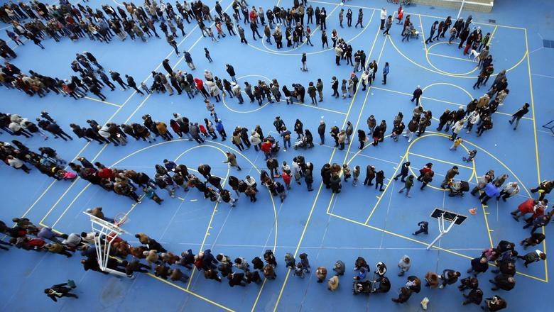 People queue at a polling station to cast their ballots in a symbolic independence vote in Barcelona, November 9, 2014. REUTERS/Albert Gea