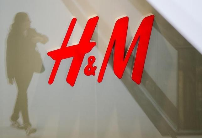 A woman is reflected next to the logo of the H&M fashion retailer in the newly opened Mall of Berlin shopping centre in Berlin, September 25, 2014. REUTERS/Thomas Peter