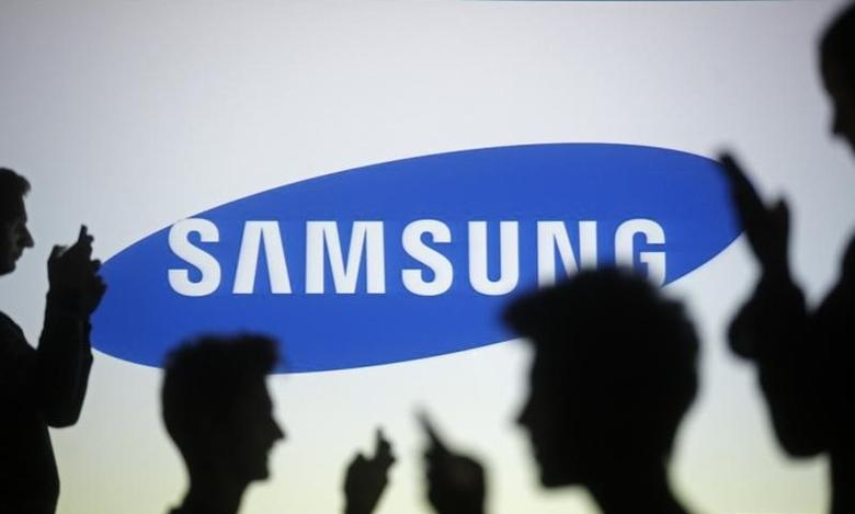 People are silhouetted as they pose with mobile devices in front of a screen projected with a Samsung logo, in this picture illustration taken in Zenica October 29, 2014.     REUTERS/Dado Ruvic