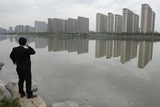 A man talks on his phone near a new residential compound in Taiyuan, Shanxi province, May 11, 2014.   REUTERS/Jon Woo