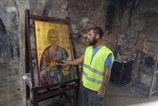 A construction worker lights a candle in front of an icon of the Apostle Andrew in a 15th century chapel at the Apostolos Andreas Monastery in Cyprus, November 11, 2014.  REUTERS/Andreas Manolis