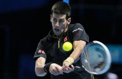 Novak Djokovic of Serbia returns the ball to Stan Wawrinka of Switzerland during their tennis match at the ATP World Tour finals at the O2 Arena in London November 12, 2014. REUTERS/Suzanne Plunkett